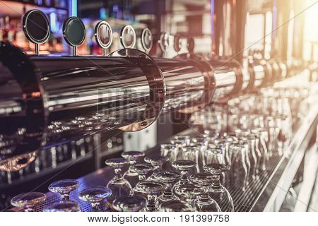 Shiny silver beer taps in pub. Beer mugs
