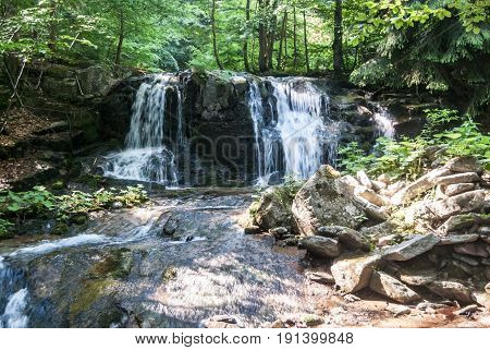 Ponikly vodopad waterfall on Ponikly potok mountain stream with forest on the background in spring Jeseniky mountains in Czech republic