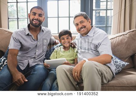 Portrait of smiling multi-generation family sitting together on couch at home