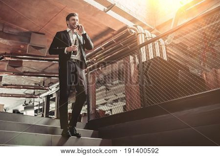 Full-length image of uccessfull businessman is drinking beer and talking on smartphone while going down the staris in bar.
