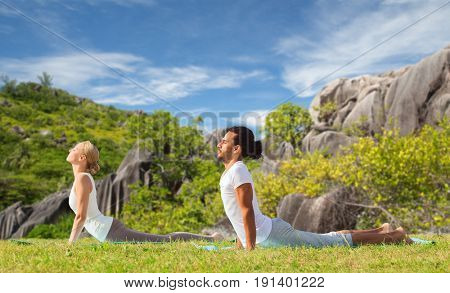 fitness, sport, relax and people concept - couple making yoga cobra pose over natural background