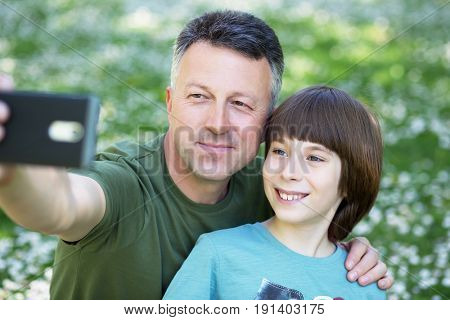 Father and son taking photo with smartphone together outdoor. Family selfie time.