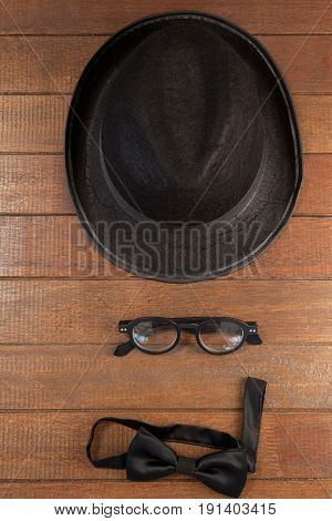 Close-up of hat, spectacles and bow tie arranged on wooden background