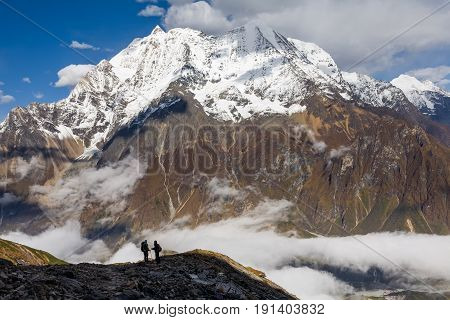 Trekker on the way to the valley covered with cloud on Manaslu circuit trek in Nepal poster