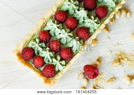 Pistachio tart. Pistachio tart on white Belgian chocolate BARRY with a layer of raspberry confit, crispy shortbread base, fading cream and juicy raspberries.A classic combination in miniature format.