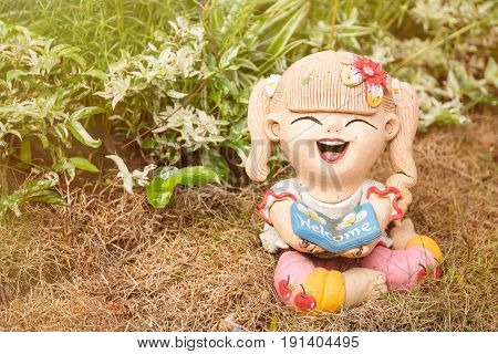 Smiling Welcome Girl Clay Doll Sitting On Green Grass Background With The Sunrise, Welcome.