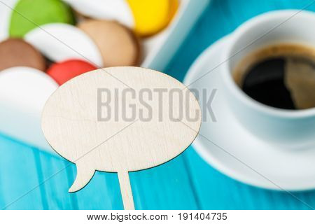 Wooden empty plate, macaroons and coffee, focus on topper