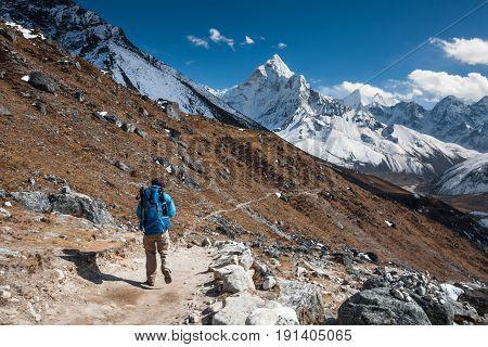 Trekker approaching Amadablan mount in Khumbu valley on a way to Namche Bazar
