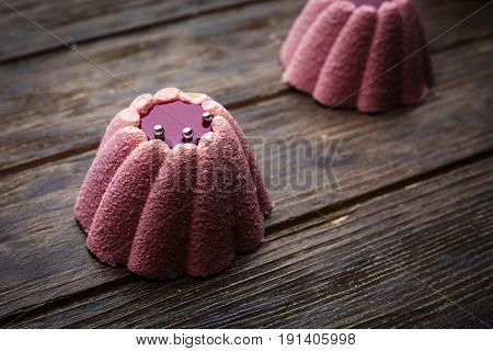 Pink Souffle cupcake in a wooden background