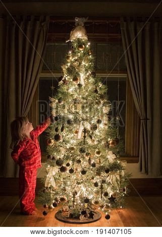 A young girl dressed in her Christmas pajamas admiring a beautifully decorated Christmas tree at night time and reaching to have a closer look at some of the ornaments.