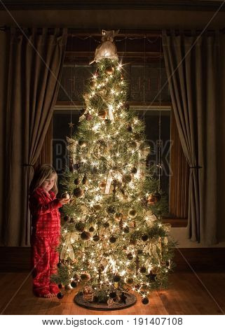 A young girl dressed in her Christmas pajamas admiring a beautifully decorated Christmas tree at night time.