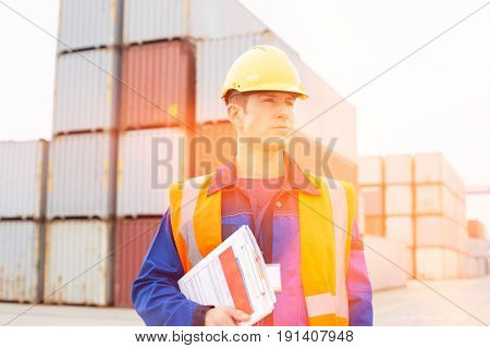 Mid adult man with clipboard in shipping yard