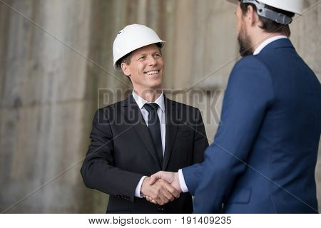 Two professional engineers in hard hats shaking hands and looking at each other