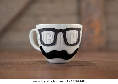 Close-up of fake moustache and spectacles on cup