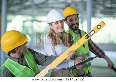 Smiling Inspector Writing On Clipboard While Standing With Workers Holding Level Tool
