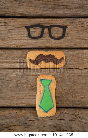 Close-up of delicious creative cookies and spectacles on wooden plank