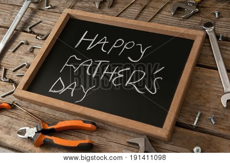 Close-up of happy fathers day message written on slate