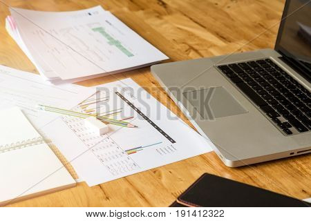Pencil, Rubber With Documents And Laptop On Wooden Desk