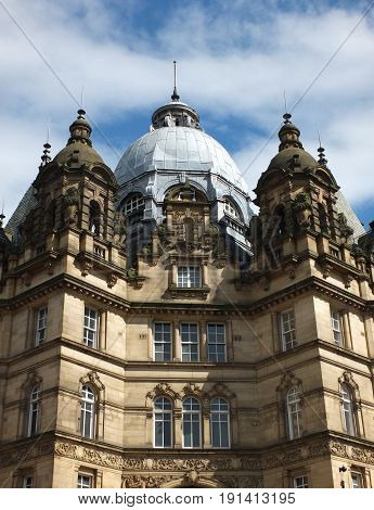 leeds market hall with decorative stonework dome and blue sky