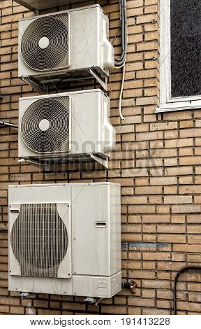 Three external air-conditioner units mounted outside on a wall