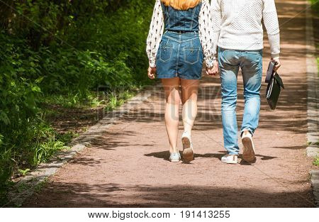 Loving couple holding hands while walking at the park