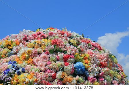 Colourful flower bed globe arrangement in blue sky