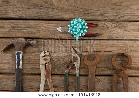 Close-up of decorated pliers and vintage worktools on wooden plank