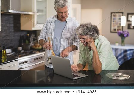 Smiling senior woman using laptop with husband in kitchen at home