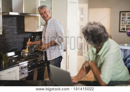Senior woman looking at smiling husband cooking in kitchen