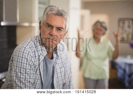 Portrait of unsmiling senior man with angry woman in background at home