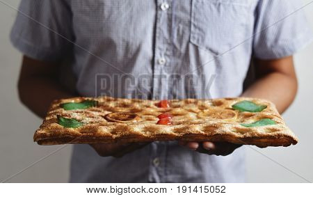 closeup of a young caucasian man holding a coca de Sant Joan, a typical sweet flat cake from Catalonia, Spain, eaten on Saint Johns Eve
