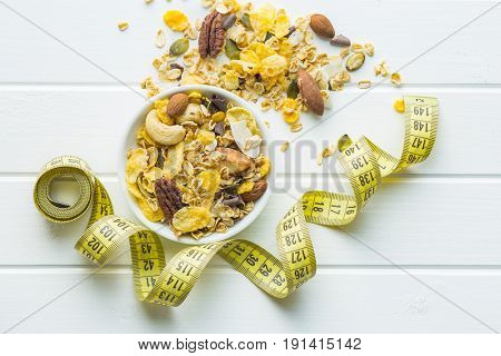 Tasty homemade muesli with nuts in bowl with measuring tape. Diet concept. Top view.