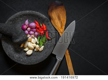 Traditional stone motar & pestle from Asia with spicy ingredients chilli garlic & small purple onions.