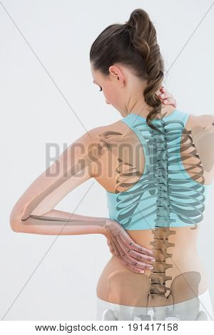 Rear view of female suffering from muscle pain against white background