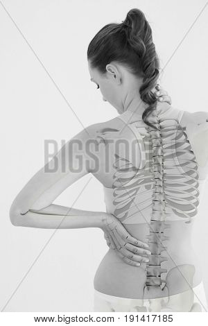Rear view of woman suffering from muscle pain against white background