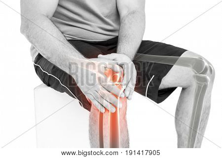 Mid section of man holding sore knee while sitting against white background