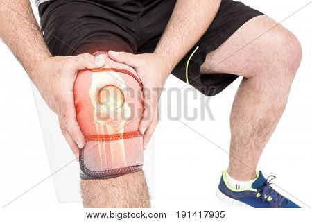 Mid section of man holding sore knee against white background