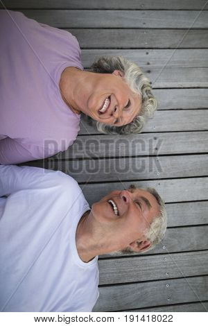 Overhead view of happy senior couple lying on wooden floor at porch
