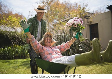 Man carrying cheerful senior woman holding bouquet in wheel borrow at backyard
