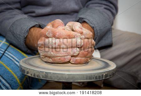 hands of potter man make clay jug