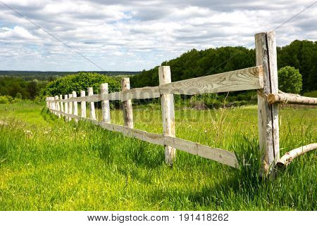Wooden fence on green meadow