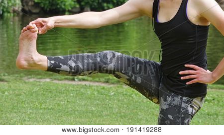 young woman exercising yoga on the grass near Lake