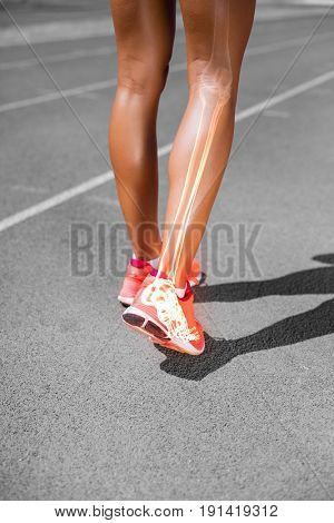 Low section of female athlete walking on sports track during sunny day
