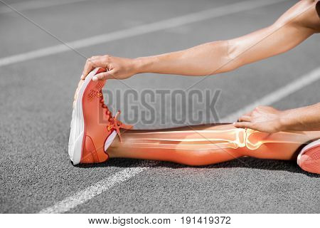 Low section of athlete stretching on track during sunny day
