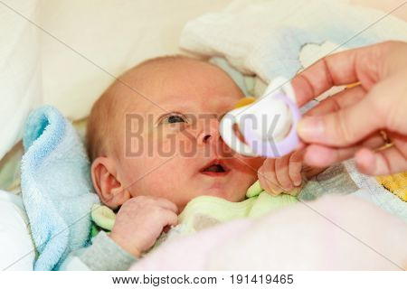 Infant care beauty of childhood concept. Little newborn baby lying calmly in bed surrounded with blankets
