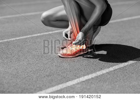 Low section of female athlete tying shoelace on track during sunny day