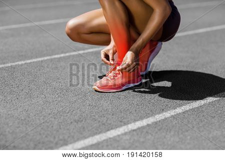 Low section of athlete tying shoelace on track during sunny day