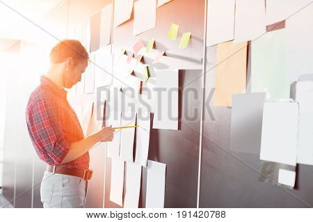 Businessman analyzing documents on wall at creative office
