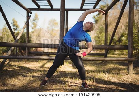 Happy woman exercising during obstacle course in boot camp