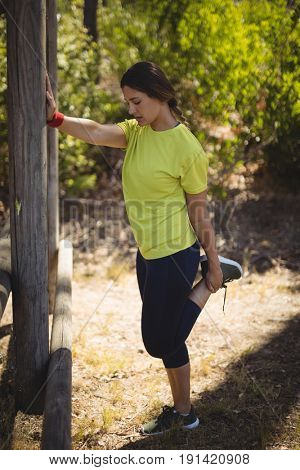 Beautiful woman performing stretching exercising during obstacle course in boot camp
